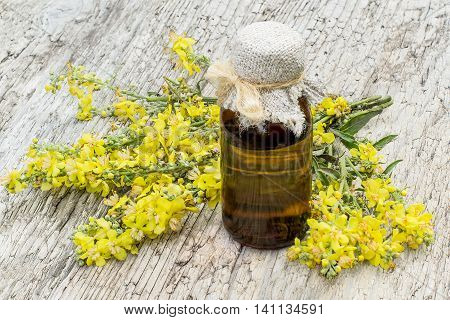Mullein also known as velvet plant (Verbascum) and pharmaceutical bottle on old wooden table. The plant is highly valued in herbal medicine it is used in the form of infusions decoctions ointments oils