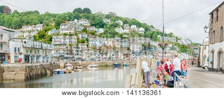 Looe England- July 23, 2013: People gather and fish on Buller Street by East Looe River in the Cornwall coastal town of with homes covering the hill on opposite side, Looe England.
