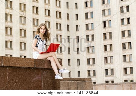 Young woman with a laptop sitting on the stairs, near the university