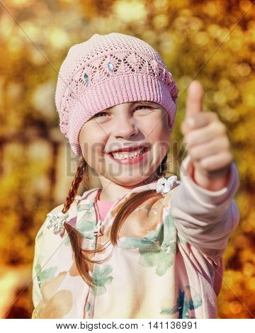 Happy child smiling showing a gesture okay on a background of autumn foliage of trees.