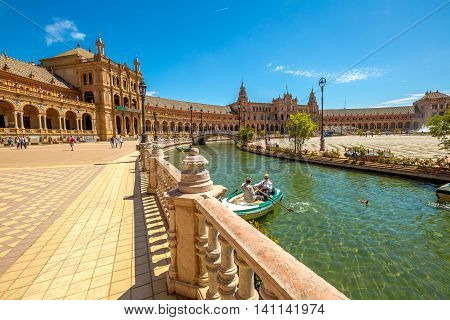 Seville, Andalusia, Spain - April 18, 2016: panoramic view of boats with tourists on canal surrounding the Plaza de Espana on a sunny day.