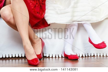 Elegance and style. Two fashionable elegant women sitting on sofa. Mother and daughter wearing dresses red shoes
