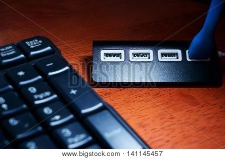 Black USB hub on the table near black keyboard under USB lamp