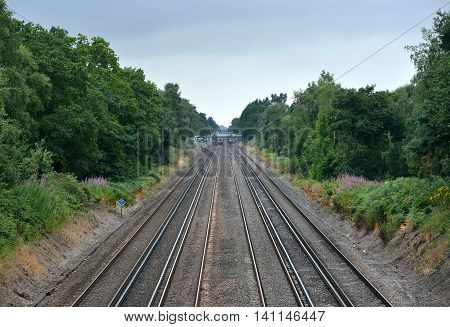 Four straight train tracks through woodland, uk