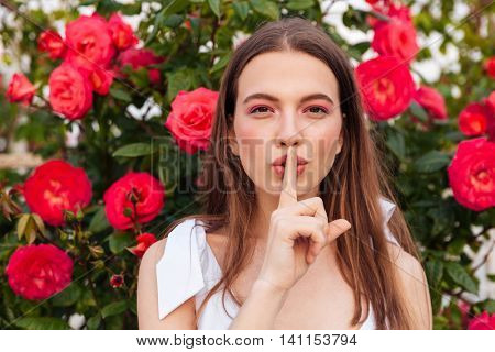 Young pretty woman making silent gesture with finger on lips over flowers background