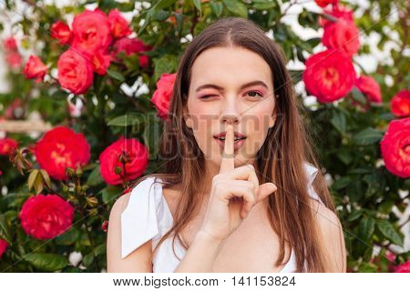 Young pretty woman making silent gesture with finger on lips and winking over flowers background