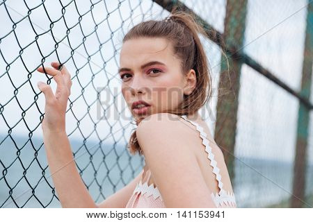 Closeup of pretty young woman with ponytail standing near chain link fence