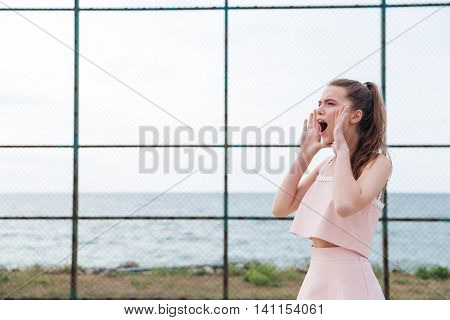 Pretty cute young woman shouting and calling for somebody outdoors