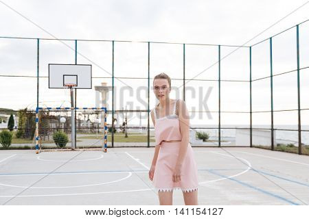 Beautiful tender young woman standing on outdoor playground