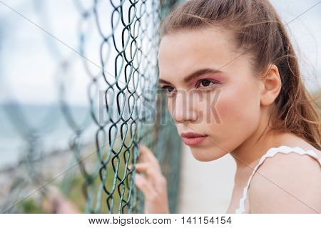 Portrait of attractive young woman looking through chain link fence