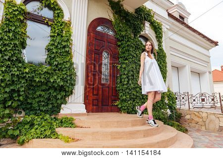 Attractive girl in white dress goes down the stairs against of an old house architecture