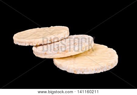 Vanilla yogurt coated puffed rice cakes on isolated black background