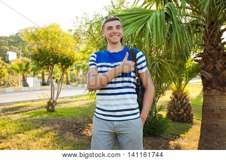 Tourist in the cap shows the finger in the cap and smiles . Behind him the backpack . The sun is shining and he's cap