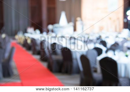 blurred tables and chairs set up for a wedding banquet