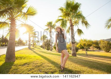 Young girl having fun in a tropical Park . Everywhere palm trees .She is dressed in a light summer dress . She's smiling and happy