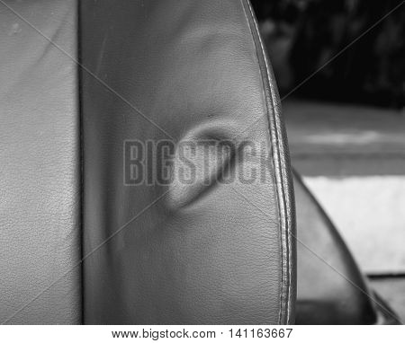 A dent pressure mark indentation on old leather vehicle car seat with selective focus and black and white effect