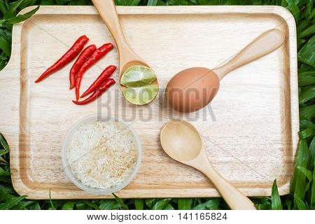 egg and sliced lime on the spoon with red chilli and rice bowl on the wooden tray