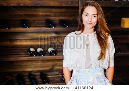 A young successful woman winemaker demonstrates his wine cellar and its wine products concept business