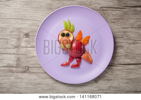 Dragon made of fruits on plate and wooden board