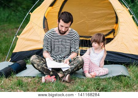 Dad and daughter plotting a route of travel on map. Active lifestyle, tourist family trip