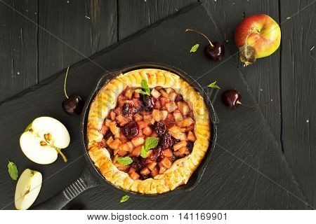 Homemade opened apple and cherry pie in an iron skillet. Top view