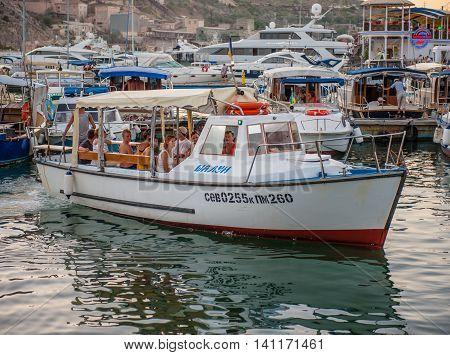 BALAKLAVA CRIMEA. UKRAINE - JULY 25 2010: tourists go on sightseeing tours on the sea in motorboats