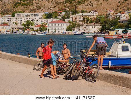 BALAKLAVA CRIMEA. UKRAINE - JULY 25 2010: Local guys on the background of the bay