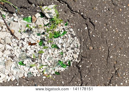 A hole in an old paved footpath covered with white stone (gravel) and broken glass.