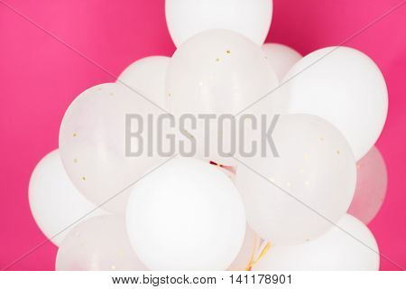 holidays, birthday, party and decoration concept - close up of inflated white helium balloons over pink background
