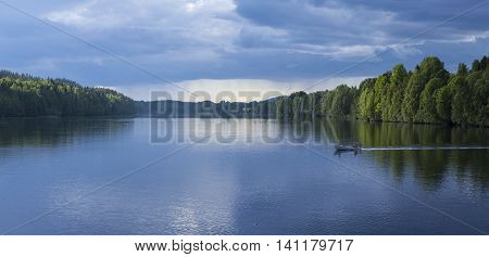 GRANO, SWEDEN ON JUNE 25. View of a Nordic river, showers and a small boat on June 25, 2016 in Grano, Sweden. Unidentified people in the boat. Editorial use.