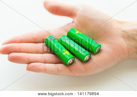 recycling, energy, power, environment and ecology concept - close up of hand holding green alkaline batteries