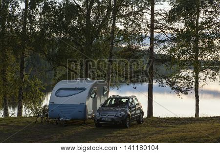 GRANO, SWEDEN ON JUNE 25. View of a campsite, car and caravan on June 25, 2016 in Grano, Sweden. Late evening after a shower, calm river in the background. Editorial use.