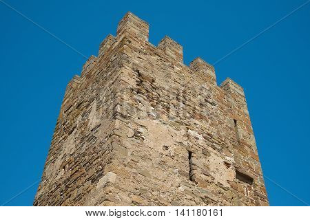 The ancient fortress tower against the blue sky. Architecture exterior