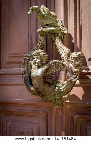ornate bronze door knocker on brown red door in Valletta Malta Europe