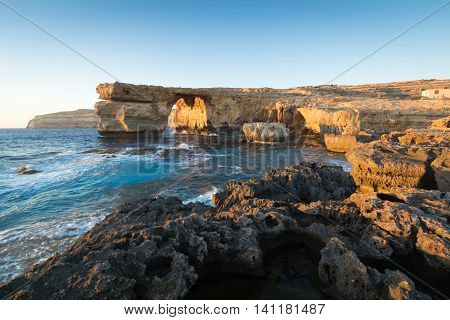 Limestone arch at sunset know as the Azure Window in Dwerja Gozo Malta. This location was used as a wedding scene in Game of Thrones as Daenerys Targaryen marries the Dothraki warlord Khal Drogo.