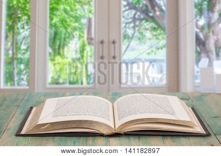 Open old book on wood background in the room