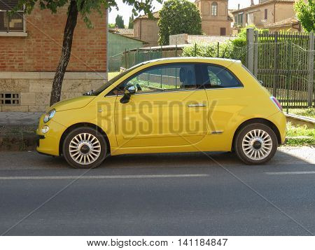 ROME ITALY - CIRCA JULY 2016: yellow Fiat New 500 car parked in a street of the city centre