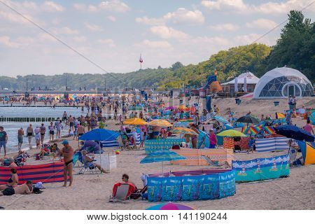 KOLOBRZEG POLAND - JUNE 23 2016: Many vacationers spend time on the sandy beach in the immediate vicinity of the pier by the Polish coast of the Baltic Sea.
