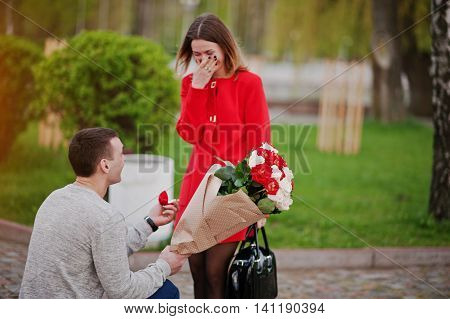 Marriage Proposal. Man With Boquet Of Flowers Kneeling And Give Engagement Ring For His Girlfriend