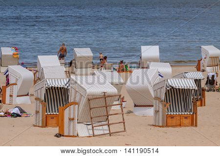 KOLOBRZEG POLAND - JUNE 23 2016: Many vacationers spend time on the sandy beach some of them sitting on wicker beach chairs.
