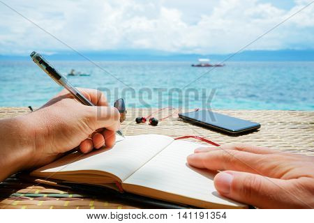 caucasian man is writing some idea, message or letter in his notepad by pen in his left hand, while he sitting on the beach of tropical sea with boat at sunny day