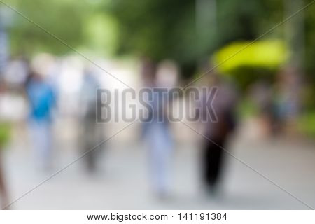 Blur image of people walking in the park with bokeh for background use.