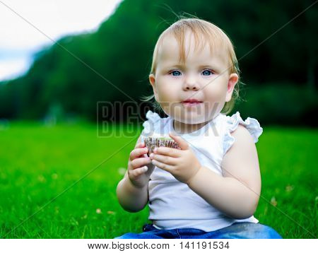 baby eating a cake outdoor in the summer park