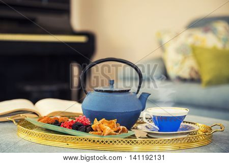 Still Life - Book, cup of tea. dried fruitsa and teapot - shallow focus