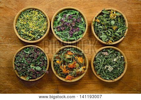 Dried herbs for use in alternative medicine.Herbal medicine phytotherapy medicinal herbs.For preparation of infusions decoctions tinctures powders ointments tea.Background wooden board
