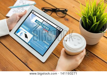 business, mass media, technology, people and advertisement concept - close up of woman with world news web page on tablet pc computer screen and coffee cup on wooden table