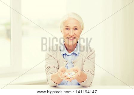 age, medicine, health care and people concept - happy senior woman with pills at home or hospital office