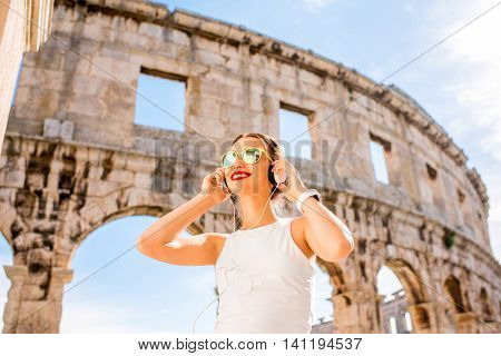 Young smiling sports woman listening to the music with headphones standing near the ancient amphitheatre in Pula city.