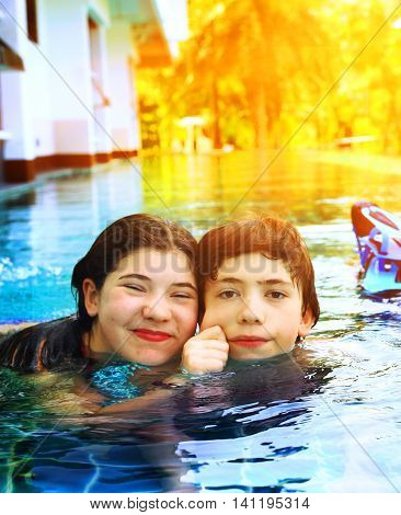 teen siblings boy and girl close up portrait in open air swimming pool in thailand