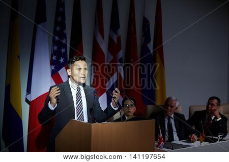 Businessman speaking about politic while standing at podium